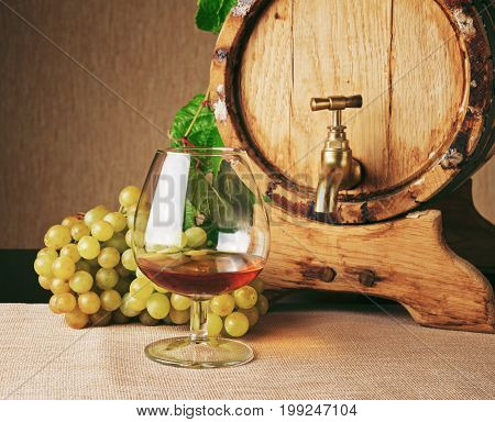 Glass Of Brandy, Bunch Of Ripe Grape And Cognac Barrel