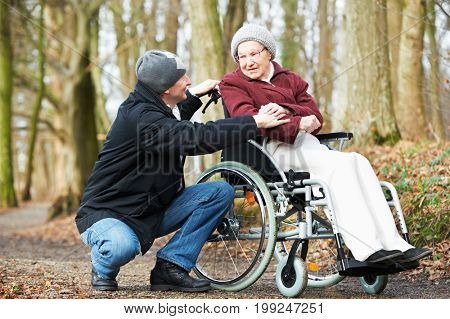 Caregiver man walking with disabled senior woman at wheelchair in nature