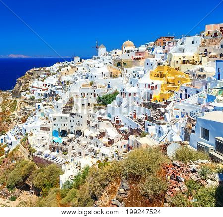 Breathtaking scenery of Oia village traditional Greek island architecture at Aegean sea and noon zenith sun flare background. Santorini island, Greece, Europe.