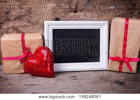 Festive gift box decorative red heart and empty blackboard on vintage wooden background. Selective focus. Place for text.