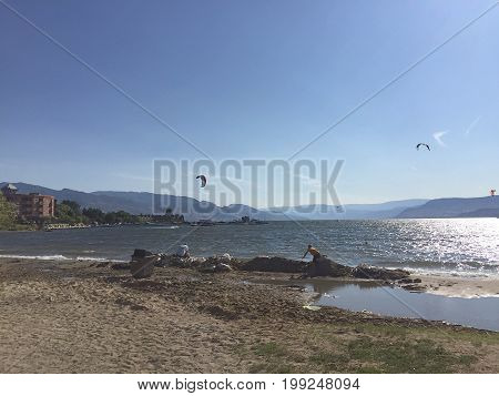 Scenic summer lake landscape. Kite surfing and people on beach. Kelowna BC Canada