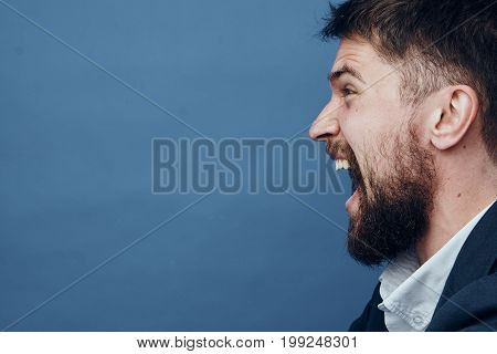 Business man with a beard on a blue background screaming, portrait, emotion.