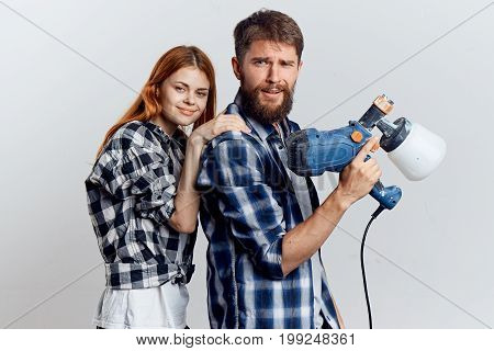 Beautiful young woman on a light background with a bearded man holding construction tools for repair.