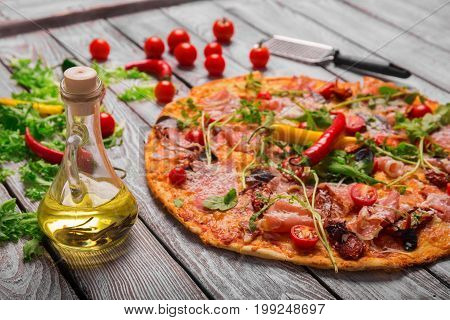 A close-up picture of a beautiful crusty carbonara pizza and a glass bottle of yellow, thick oil on a blurred wooden background. A metal scapula and red tomatoes next to a pizza with juicy vegetables.