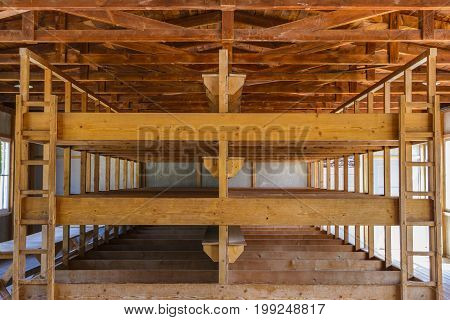 Dachau Concentration Camp Germany - July 30 2016: Inside sleeping quarters with wooden bunk beds from barrack room showing terrible prisoners living conditions from extermination camp.