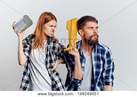 Beautiful young woman with a bearded man on a light background holding construction tools, quarrel.