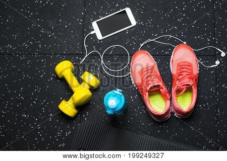Macro picture of gym accessories for sports training on a black background. Blue sportive bottle, orange training shoes, yellow dumb-bells, black pilates mat. Training concept.