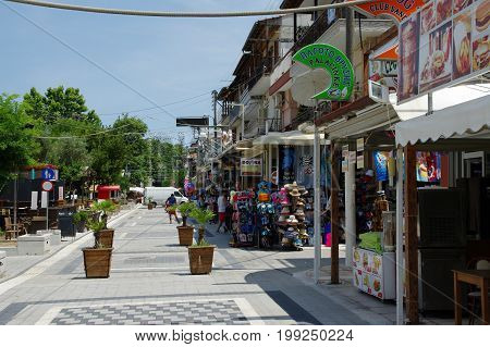 Stavros Greece - June 15 2017: small town near the Chalkidiki peninsula in northen Greece region of Macedonia. Main street in the city with shops and pubs. Shops mainly offer beach equipment and clothing. On the street there are some tourists.