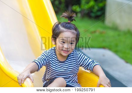 Cute Boy Playing Slider In The Playground.