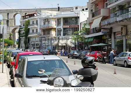 Kavala Greece - June 16 2017: city in the northern Greece in the Macedonia-Thrace region located on the Aegean Sea. Street in the city center. There are many shops and in the background you can see a Roman aqueduct from the 16th century.