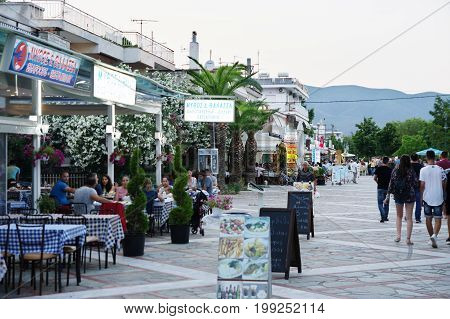 Asprovalta Greece - June 16 2017: summer resort in northern Greece on the Aegean Sea. Seaside boulevard in the evening. There are taverns and restaurants along the boulevard. On the boulevard some tourists are strolling.
