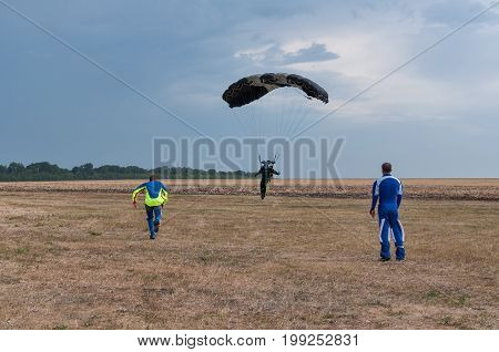 Parachutist running after landing in a field.