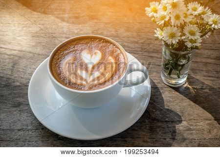 Cup of coffee with beautiful Latte art, Hot latte coffee in white cup on vintage wooden table background, Natural light