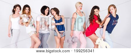 Girls in pajamas posing in studio. Happy female friends making pajama party. Women day, celebration, friends, bachelorette party, friendship, birthday and holidays concept. Banner for website