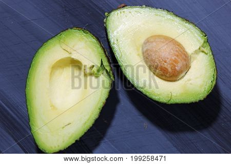 Cut up Avocado with pit on wooden background