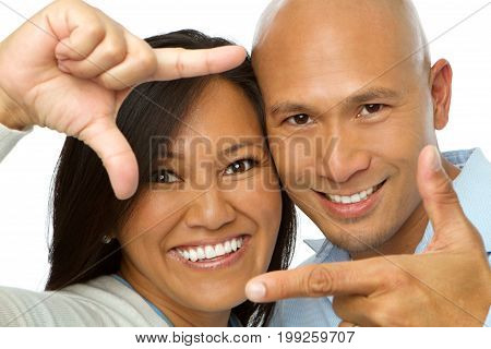 Asian couple making picture hand gestures isolated on white.