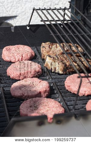 Hamburgers and steaks being grilled on the barbecue