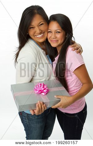Asian daughter giving a gift to her mom.