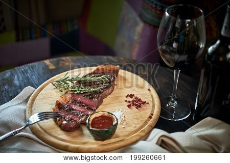 Sliced medium rare grilled steak on rustic cutting board with rosemary and spices , dark rustic metal background, top view, place for text