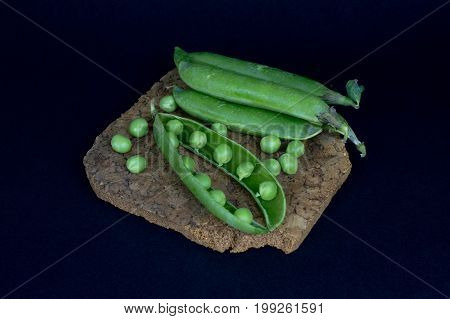 Fresh green peas lie on the cork substrate on a black background. Top view