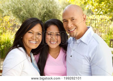 Happy Asian family hugging isolated on white.