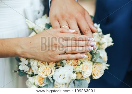 beautiful manicured hands of the bride and groom at a wedding bouquet