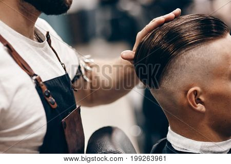 hairdresser in barbershop corrects the hairstyle for the client to the man, the hair is laid back, the whiskey is shaved.