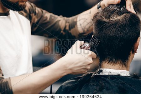 Close-up of a young hipster guy in a barbershop hairdresser cutting hair with scissors and a typewriter, waxing hair, blow-drying. Concept men's place, toned photo. Soft focus.