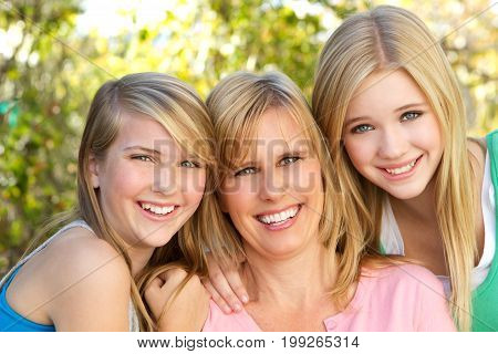 Portrait of a happy mother and her teenage girls smiling.