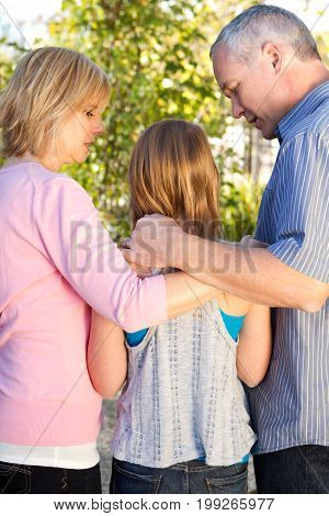 Parents talking with their teenage daughter outside.