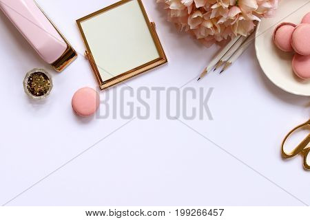 Chic styled desk top with gold, pink and white office supplies, flowers, cookies and glitter. Copy space.