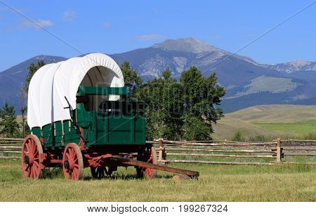 Old western covered wagon and mountain in green pastures