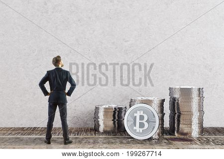 Back view of young businessman looking at silver bitcoin piles in room with concrete wall and wooden floor. E-commerce concept. 3D Rendering