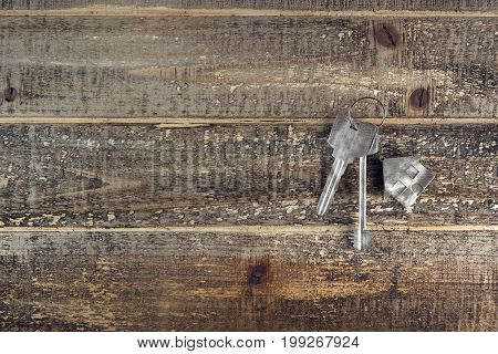 Aged silver keys with house keychain on textured wooden surface with copy space. Mortgage concept. 3D Rendering