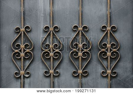 A fragment of gray doors with forged bars and a beautiful pattern