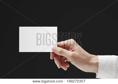 Businessman hand holding empty business card on dark background. Advert concept. Mock up