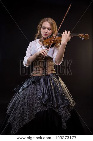 Blond young woman playing the fiddle on black background