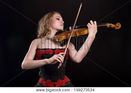 Woman in dress playing the fiddle on black background