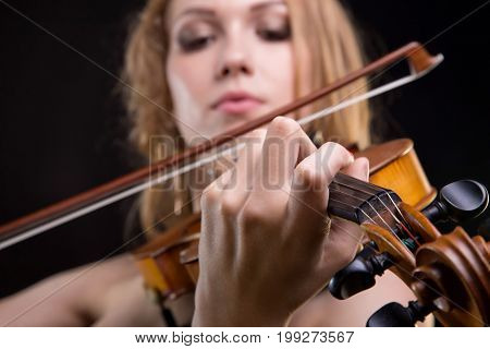 Closeup photo of girl playing the fiddle on black background