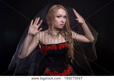 Blond woman wearing black veil on black background