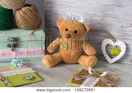 Soft toy bear. Toy bear on the table with a heart and handmade cards
