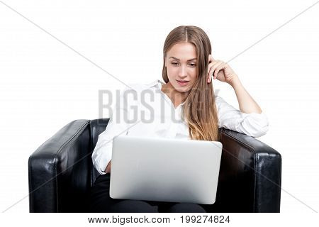 Isolated portrait of a blonde businesswoman wearing a white blouse and sitting in a leather armchair with her laptop. She is looking at the screen with an amused expression.