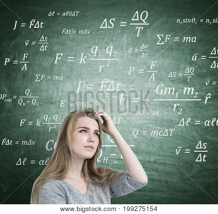 Close up of a blonde businesswoman scratching her head and thinking. She is wearing a gray sweater and trying to recall an idea. Chalkboard with formulas