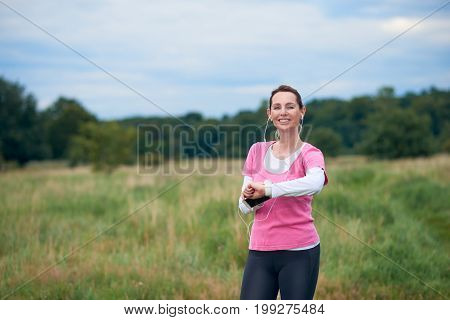 A healthy smiling woman in fit wear with smart phone watch and earphones exercising outdoors in nature.