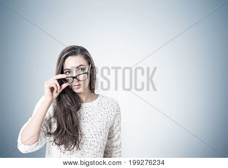 Portrait of a young woman with dark long hair wearing a white sweater and holding her glasses with a thick frame. She is looking to the distance. Gray wall. Mock up