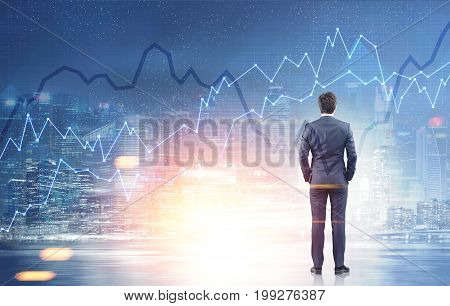 Rear view of a businessman standing with his hands in suit pockets and looking at a night cityscape with graphs. Toned image double exposure mock up