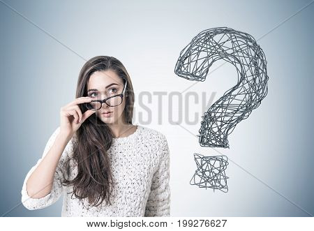 Young woman with dark long hair is wearing a white sweater and holding her glasses with a thick frame. She is looking to the distance while standing near a gray wall with a question mark