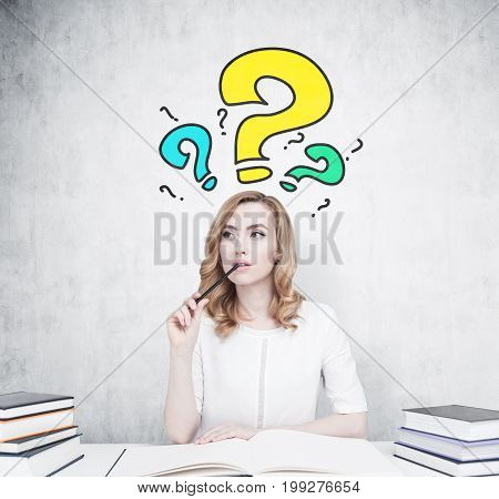 Beautiful young woman is sitting at a table with piles of book on it. The one in front of her is open. She is thinking and biting a pencil. Concrete wall with blue and yellow question marks