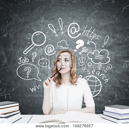 Beautiful young woman is sitting at a table with piles of book on it. The one in front of her is open. She is thinking and biting a pencil. Blackboard with an internet search sketch