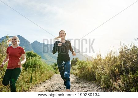 Two Women Cross Country Running Together On A Trail